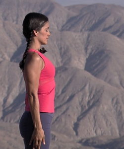 Woman practicing the mountain pose with backdrop of mountains